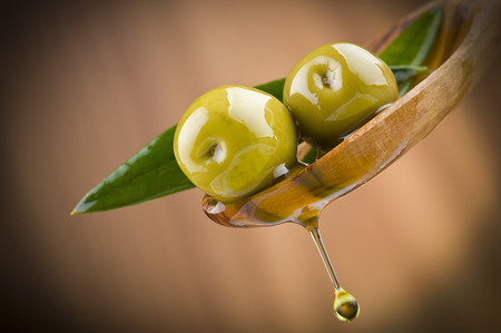 Two olives and leaves with drop oil on wood spoon Stockfoto