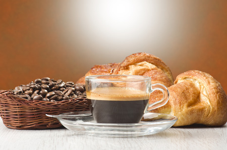 expressed: coffee in glass cup with croissants and coffee beans