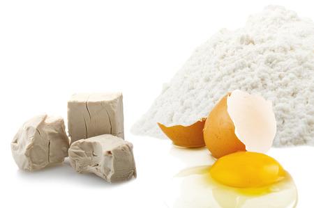 levadura: Harina, huevos y levadura cubos de cerca en el blanco Foto de archivo