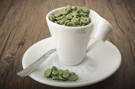 unprocessed: Cup of coffee with green coffee beans on the wood