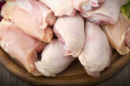 muslos: Fresh skinless chicken thighs and legs on cutting board