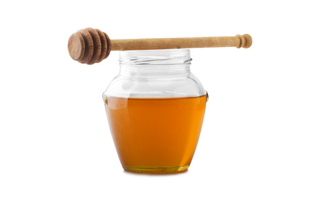 drizzler: Glass jar of honey with wooden drizzler on a white