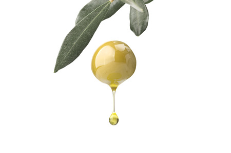 A drop of olive oil falling from one green olive on a white