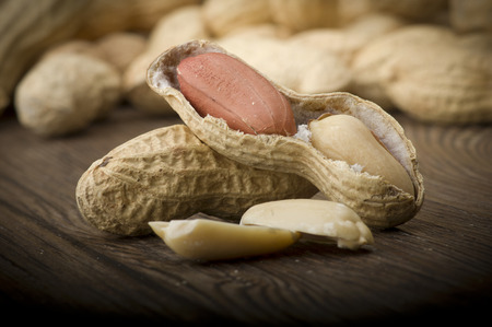 monkey nut: Peanuts in shells close up on the wood table Stock Photo