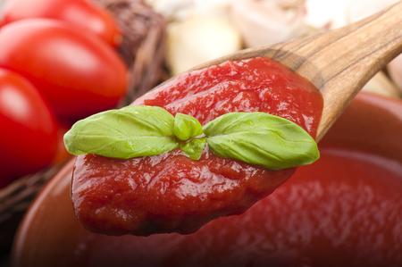 cuchara de madera con salsa de tomate y albahaca