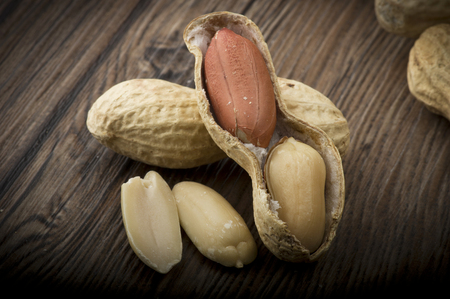 goober: Peanuts in shells close up on the wood table Stock Photo