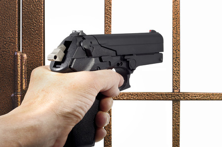 Thief armed with a pistol in front of a gate Stock Photo