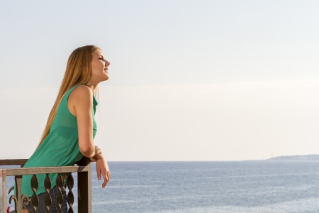 Beautiful woman looking ahead and smile with the sea in the background photo
