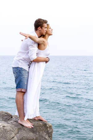 Couple young in love on cliff with background of blue sea photo