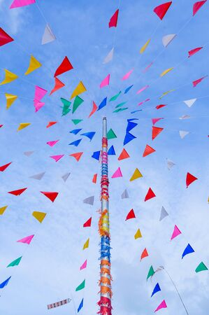 vivid color of Thai's style fancy party flag strips decoration on a fancy still pole with blue sky and white cloud in background