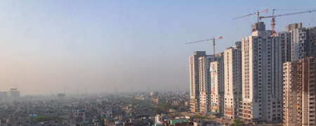 March 27, 2017 at Ghaziabad, India, Mechanical cranes in work on the buildings under con.struction and smog in air