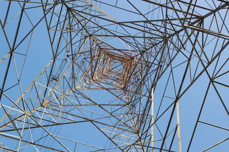 Low angle POV shot of a Transmission Tower against blue sky in Conventional power concept. Stock Photo