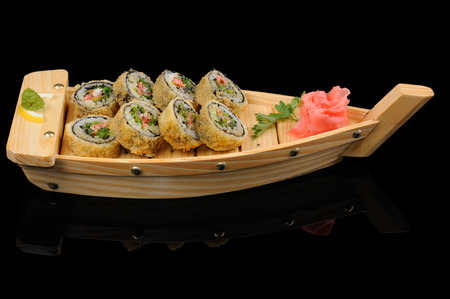 Hot japanese rolls served in small wooden boat photo