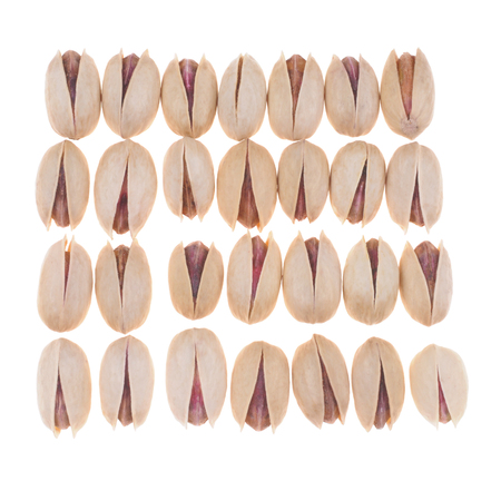 Many pistachio nuts placedin order on white background photo