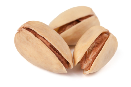 Three pistachio nuts isolated on white background photo