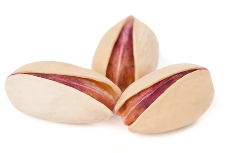 Three natural pistachios isolated on white background photo