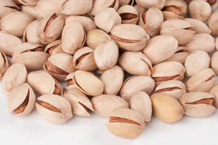 Many natural pistachios isolated on white background photo