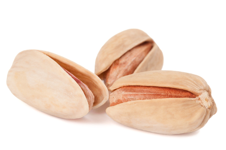 Close-up of three pistachios isolated on white background photo