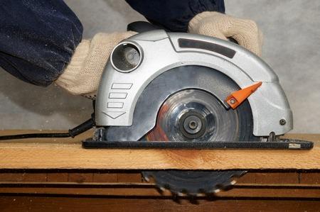 Wood cutting with circular saw photo
