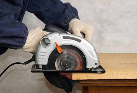 Work goes on with electric circular saw photo