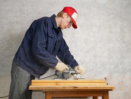 planos electricos: Joven carpintero cepilla el tablero con cepillo el�ctrico
