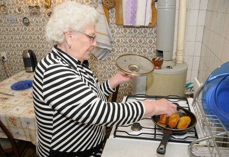old gas stove: Senior woman prepares food in her kitchen