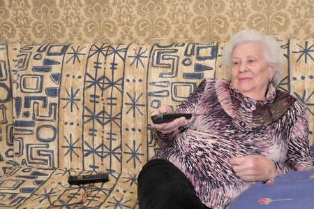 Senior woman switches channels on the TV set Standard-Bild