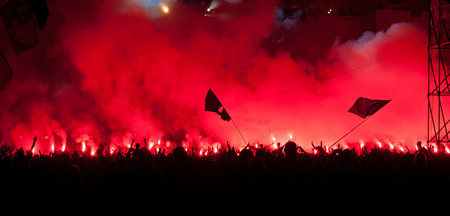 Fans burn red flares at rock concert
