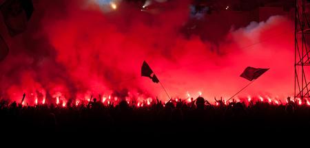 concierto de rock: Fans queman bengalas rojas en el concierto de rock