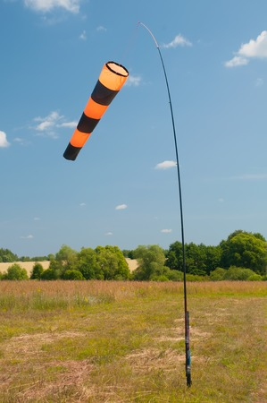 Striped windsock shows direction of the wind photo