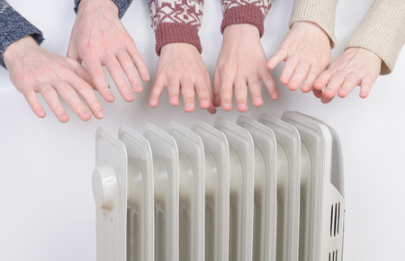 가족은 전기 히터를 통해 손을 따뜻하게