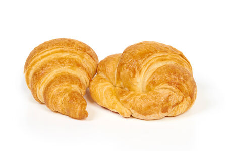 Two fresh and tasty croissants isolated on white