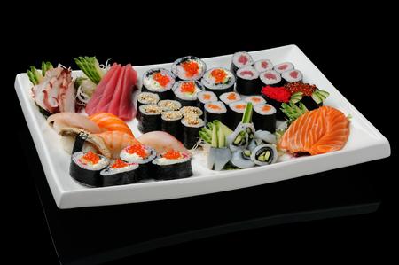 comida japonesa: Surtido de rollos, sushi y sashimi servido en plato blanco Foto de archivo