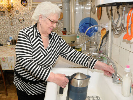 Senior woman pours water to the kettle