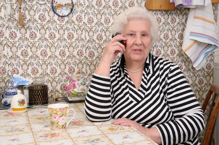 Senior woman speaks on the mobile phone in her kitchen photo