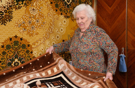 Senior woman straightens rug on her bed photo