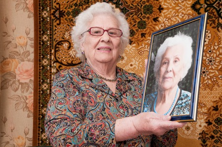 recently: Senior woman proudly shows her portrait made recently