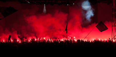 Fans burn red flares at rock concert photo