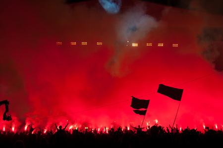 Fans burn red flares at rock concert