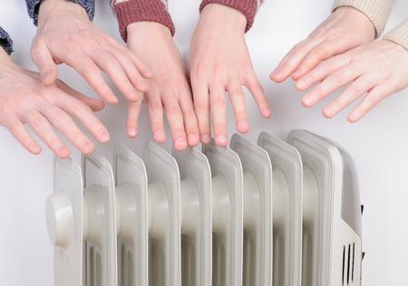가족은 전기 히터 위에 손을 따뜻하게