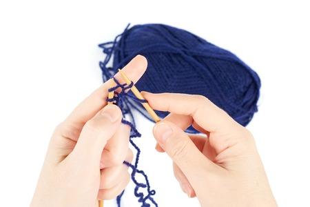 uses: Woman uses blue yarn for knitting, isolated