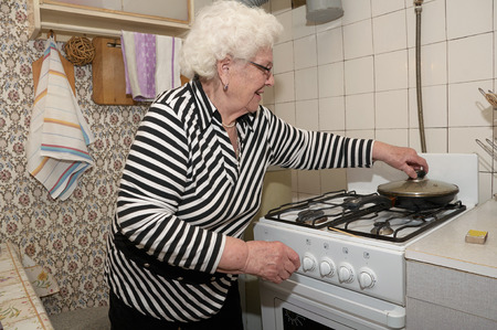 active people: Senior woman prepares food on the gas stove in her kitchen. She takes cover of the frying pan.