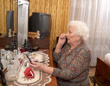 powder room: Puts mujer cauc�sica senior cerca de noventa a�os de edad en la cara en polvo antes del espejo en su dormitorio