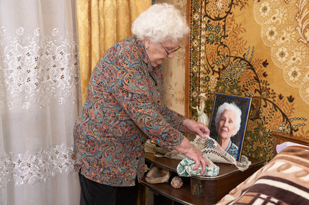 bedside table: Senior caucasian woman about ninety years old wipes the dust from the bedside table in her bed room. Her framed portrait stands on bedside table.