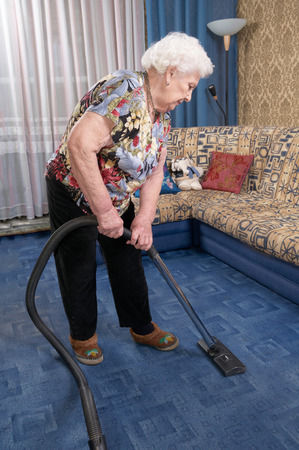 Senior caucasian woman about ninety years old runs vacuum cleaner, She cleans blue carpet in her room Stock Photo