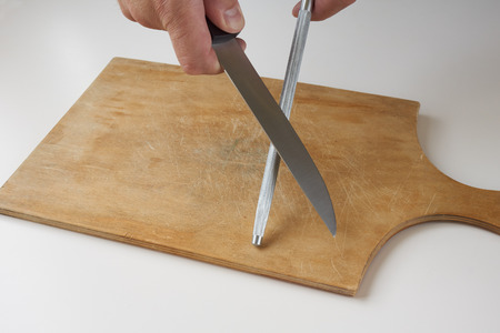 honing: Man hones knife with knife sharpener on wooden cutting board
