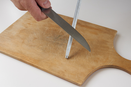Man sharpens knife with knife sharpener on wooden cutting board
