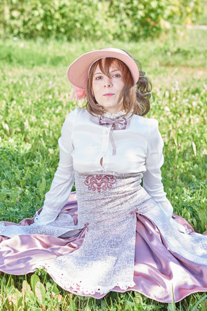 bourgeoisie: Girl with hat dressed in retro style sits on the lawn