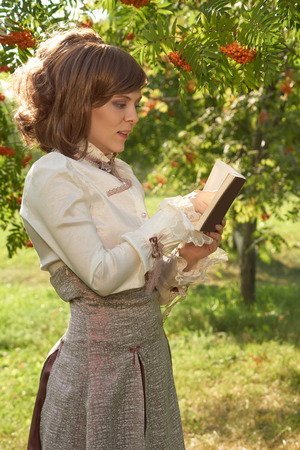 bourgeoisie: Beautiful girl dressed in old style points to the book that she reads in summer park Stock Photo