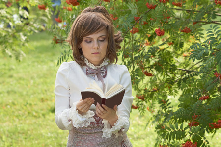 bourgeoisie: Retro dressed girl leafs through the book in the summer park Stock Photo